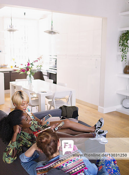 Young women friends hanging out  using smart phones on apartment sofa
