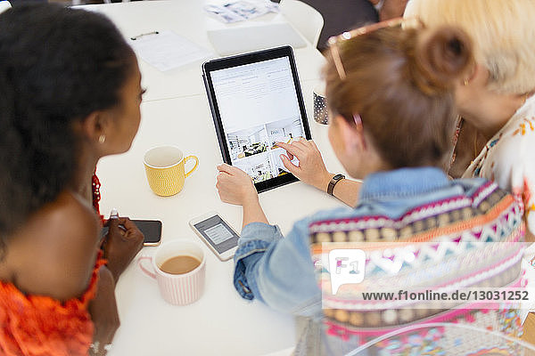 Young women friends drinking coffee and using digital tablet