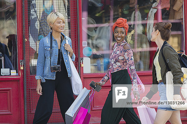Young women friends shopping  walking on urban sidewalk