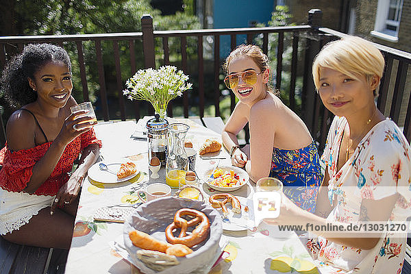 Portrait smiling young women enjoying brunch on sunny balcony
