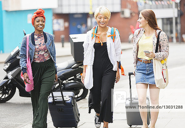 Smiling young women friends with suitcases walking on urban sidewalk