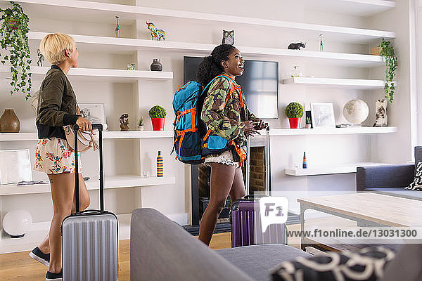 Young women friends with suitcases arriving at house rental