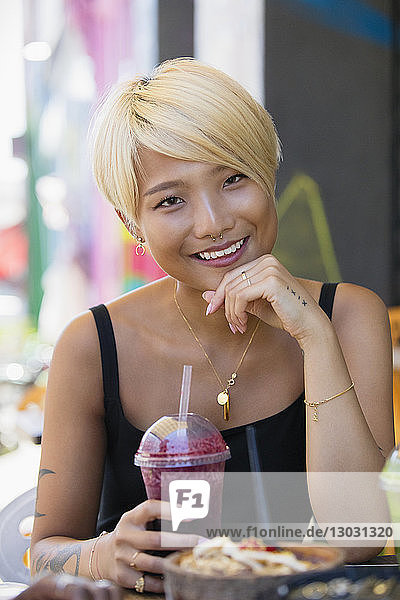 Portrait smiling  confident young woman drinking smoothie at sidewalk cafe