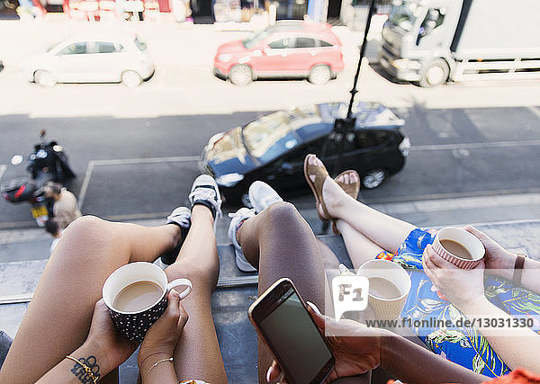 Women friends drinking coffee  dangling legs out urban apartment window