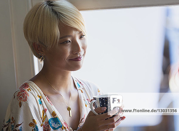 Smiling young woman drinking coffee