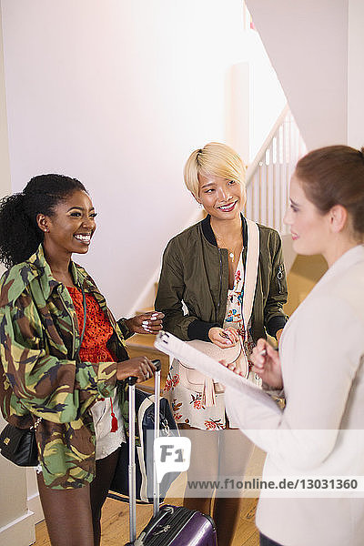 Real estate agent talking to young women with suitcases in house rental