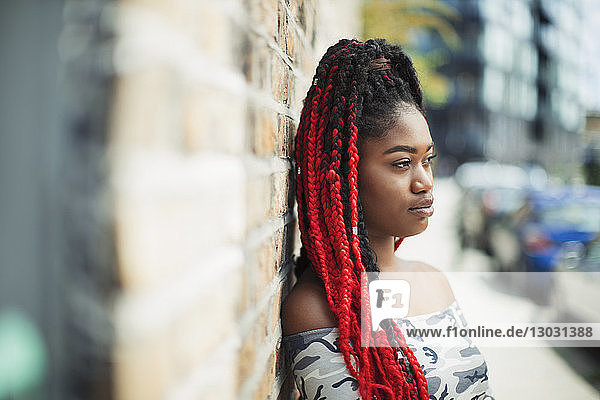 Confident young woman with red braids looking away on urban street