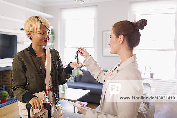 Real estate agent giving house rental keys to young woman