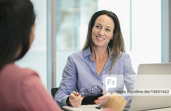 Smiling  confident businesswoman listening in conference room meeting