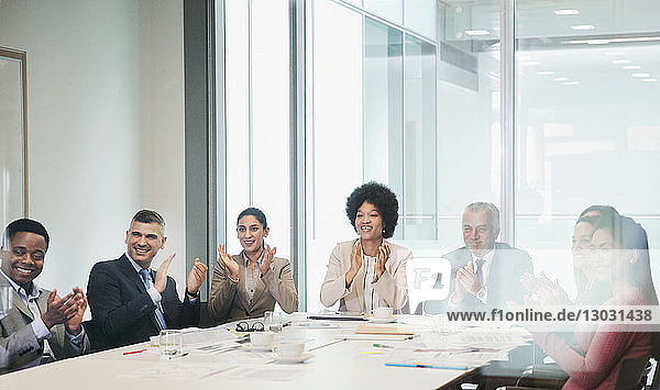 Happy  supportive business people clapping in conference room meeting