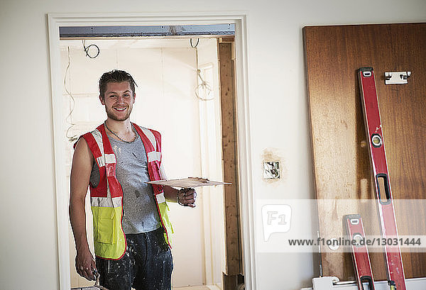 Portrait smiling construction worker plastering in house