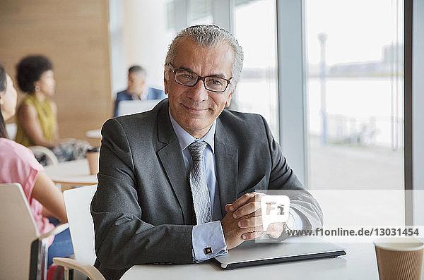 Portrait confident businessman in cafeteria