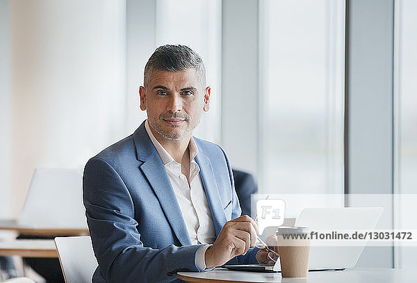 Portrait confident businessman working at laptop and drinking coffee