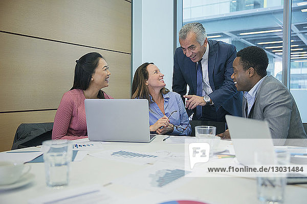 Smiling business people using laptop in conference room meeting