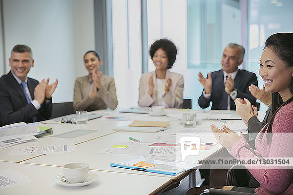 Smiling business people clapping in conference room meeting