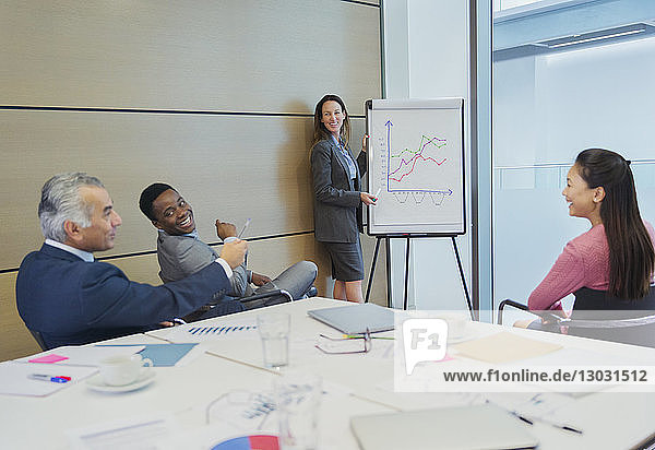 Smiling businesswoman at flip chart leading conference room meeting