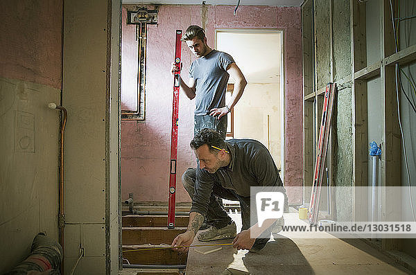 Construction workers using tape measure and level tool in house