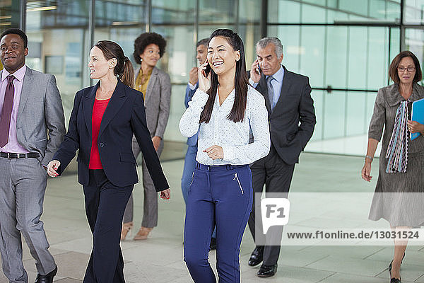 Smiling businesswoman talking on cell phone and walking