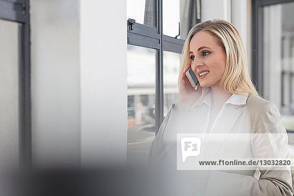Geschäftsfrau benutzt Smartphone im Büro