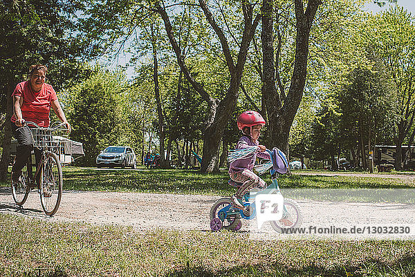 Female toddler and her grandmother cycling in park