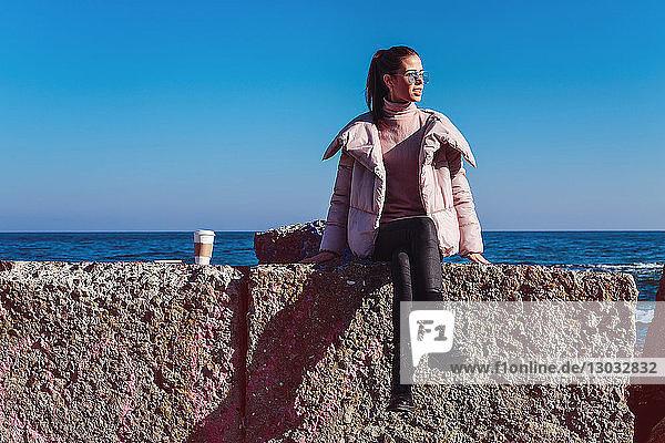 Stilvolle Frau im mittleren Erwachsenenalter auf Seemauer sitzend  Odessa  Odeska Oblast  Ukraine
