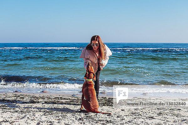 Stylische Frau mittleren Alters am Strand  die ihren Hund streichelt  Odessa  Odeska Oblast  Ukraine