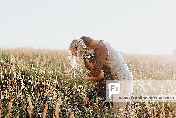 Romantischer Mann umarmt seine Freundin im sonnenbeschienenen langen Grasfeld
