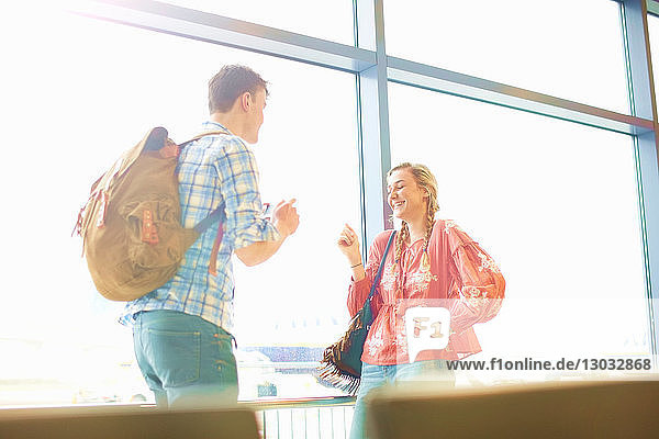 Young couple at airport  man photographing woman using smartphone