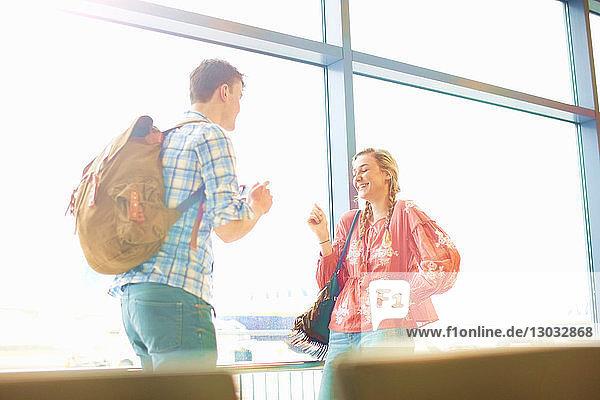 Junges Paar am Flughafen  Mann fotografiert Frau mit Smartphone