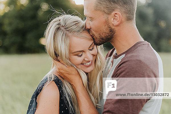 Romantic man kissing girlfriend on forehead in field
