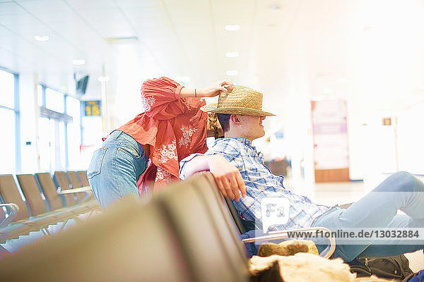 Young man sitting at airport  young woman putting her hat on his head