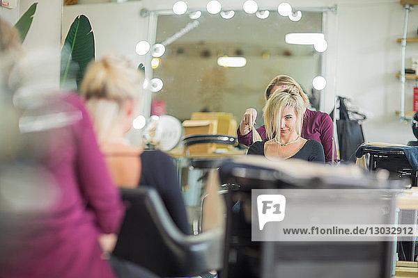 Friseur frisiert die Haare des Kunden im Salon