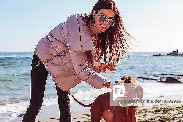 Stilvolle Frau mittleren Alters am Strand  die ihren Hund streichelt  Porträt  Odessa  Odeska Oblast  Ukraine