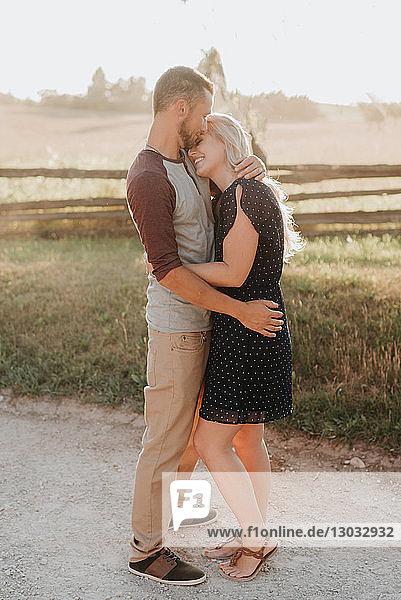 Romantischer Mann küsst auf ländlichem Feldweg seine Freundin auf die Stirn
