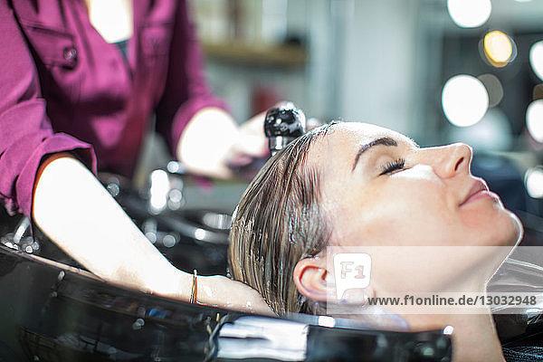 Friseur spült den Kunden im Salon die Haare