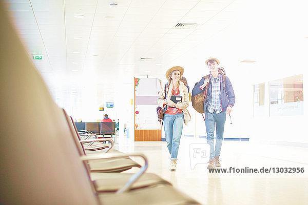 Junges Ehepaar am Flughafen mit Rucksäcken  Blick aus niedrigem Winkel