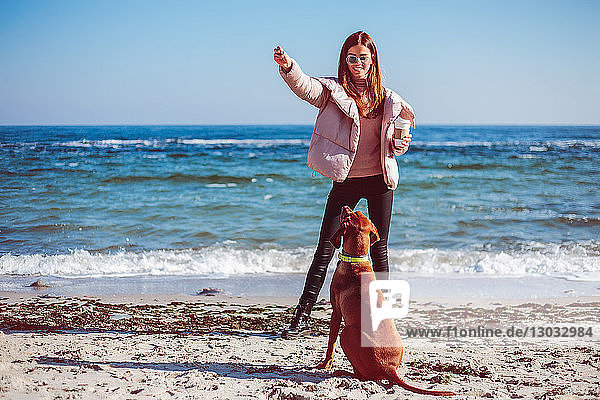 Mittlere erwachsene Frau am Strand beim Training ihres Hundes  Odessa  Odeska Oblast  Ukraine