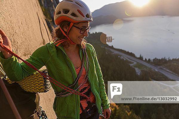 Junge Bergsteigerin blickt bei Sonnenuntergang vom Chief herunter  Squamish  Britisch-Kolumbien  Kanada