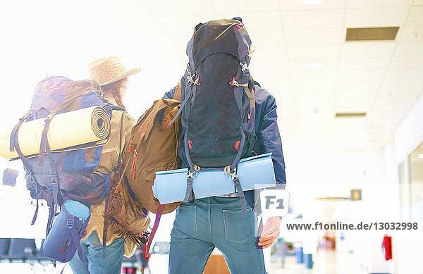 Junges Paar am Flughafen  Rucksäcke tragend  Rückansicht