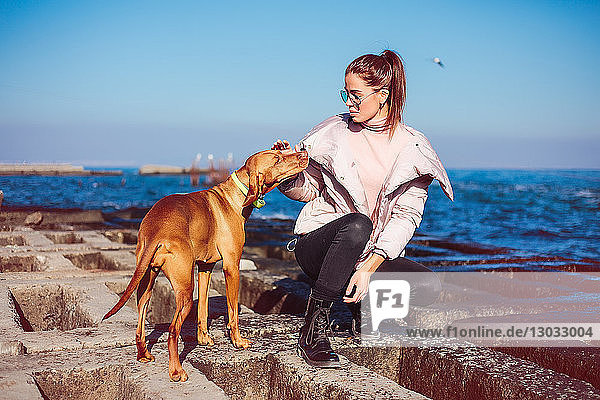 Stilvolle  mittelgroße  erwachsene Frau  die auf der Seeverteidigung kauert und ihren Hund streichelt  Odessa  Oblast Odeska  Ukraine