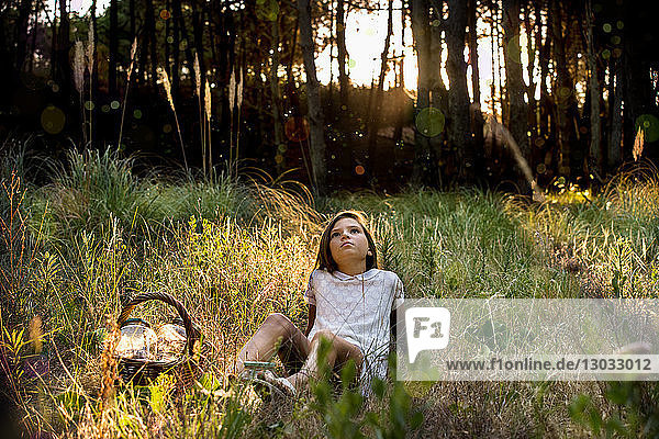 Girl with picnic basket reclining in sunlit forest gazing upward