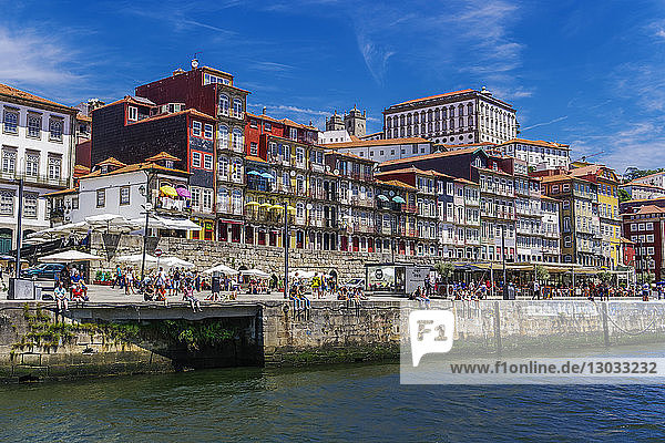 Traditional waterfront houses in the Ribeira district on the Douro River with crowd on river bank  Porto  Portugal