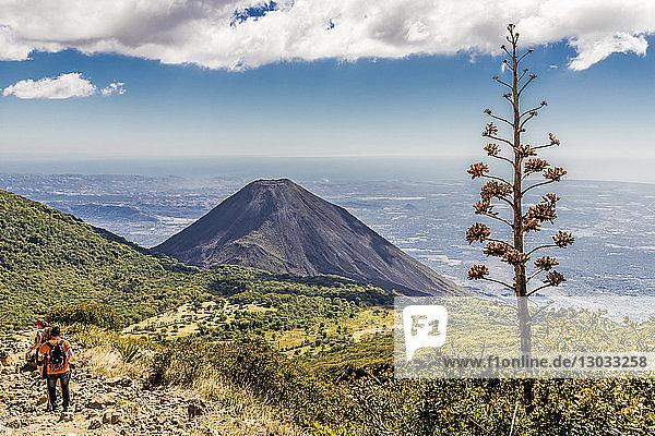 A view of Volcano Izalco and a hiker from Volcano Santa Ana (Ilamatepec ) in Santa Ana  El Salvador  Central America