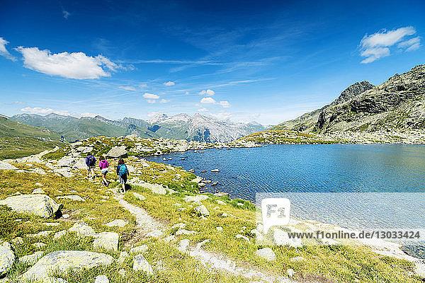 Hikers on footpath on the shore of lake Bergsee  Spluga Pass  canton of Graubunden  Switzerland