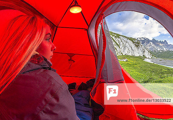 Young girls looks out of a red tent  Unterer Segnesboden  Flims  District of Imboden  Canton of Grisons (Graubunden)  Switzerland