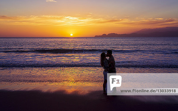 Sunset and couple in love near the Golden Gate Bridge  Baker Beach  San Francisco  California  United States of America  North America