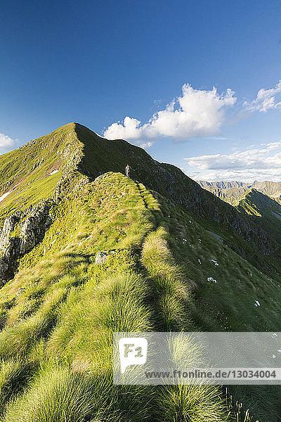 Hiker on steep ridge on the ascent towards Monte Azzarini  San Marco Pass  Albaredo Valley  Orobie Alps  Lombardy  Italy