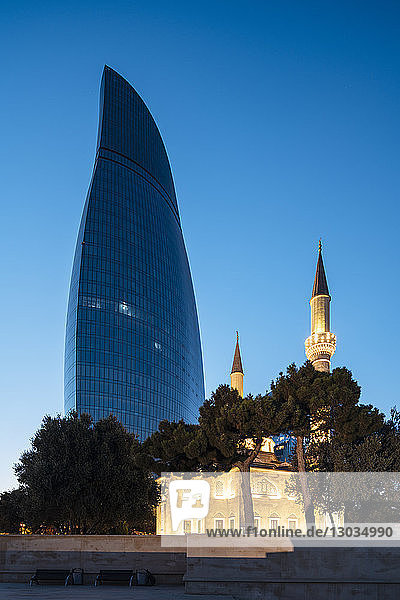 Exterior of The Shahid Mosque with Flame Towers in background at night  Baku  Azerbaijan  Central Asia