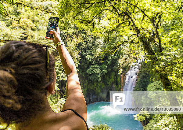 A tourist taking a picture of the Rio Celeste waterfall in Tenorio Volcano National Park  Costa Rica  Central America