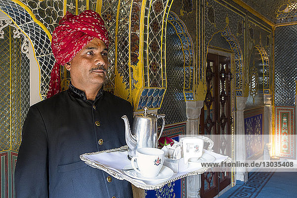 Waiter carrying tea tray in ornate passageway  Samode Palace  Jaipur  Rajasthan  India